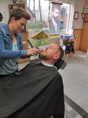 Barbier Ingrid verzorgd een baard