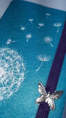 Stickmotiv Pusteblume uni in weiß auf Filz in lago mit Metalldeko Schmetterling K und Strasssteinchen (Stickdatei von Rock-Queen)