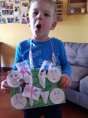Jaron hat seine Kindergartenhausaufgabe erledigt und zeigt, wie ein überraschtes Gesicht aussieht.