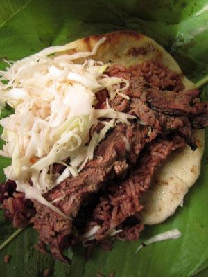 Tortilla mit Krautsalat, Rindfleisch und Bohnen im Bananenblatt serviert.