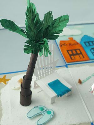 Die Palme ist unter dem weißen Papier verankert und festgeklebt, damit sie stabiler ist. Dann wurde sie Stück für Stück aufgebaut. Zum Schluss werden die Blätter angeklebt.