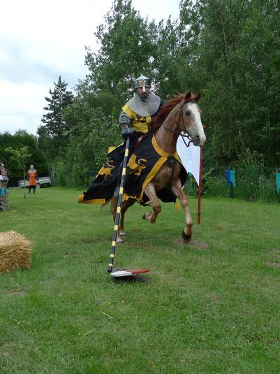 Chaque chevalier tente, à l'aide de sa lance, de renverser des écus posés en équilibre sur le sol.