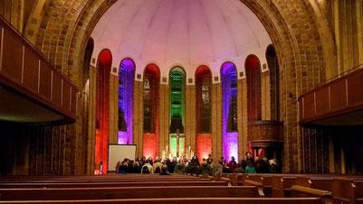 Offenes Gospelsingen: Blick auf den farbig beleuchteten Altarraum der MLGK
