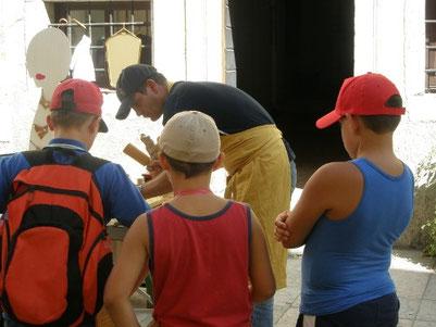 Giovanni scolpisce e tre bambini curiosi ed attenti lo guardano
