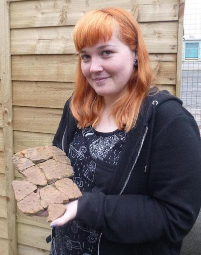 L'archéologue Sarah Carter tient une urne funéraire de l'âge du bronze extraite du site.