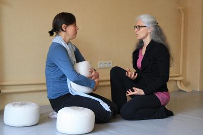 Eine Frau erklärt einer anderen Frau etwas über Energiearbeit, eine Frau hält ein Yogakissen in der Hand, beide sitzen auf Yogakissen auf dem Boden in einem Yogastudio oder einem Coachingstudio