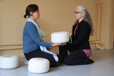 ein Yogakissen wird von einer Frau zu einer anderen Frau übergeben, beide sitzen auf dem Boden in einem Yogastudio oder Coachingstudio