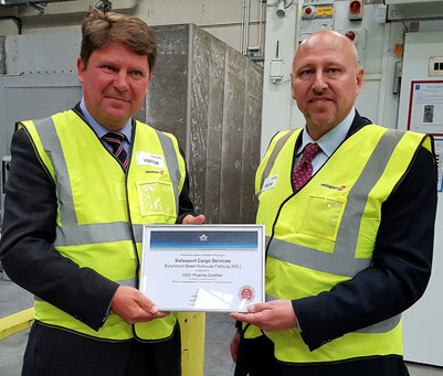 IATA Cargo helmsman Glyn Hughes (standing right) hands over the CEIV Pharma certification to Swissport CCO Nils Knudsen – photos: hs