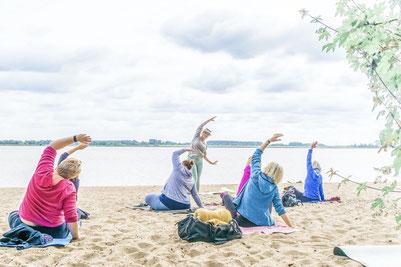 Eine Gruppe praktiziert Yoga am Elbstrand mit Blick aufs Wasser unter Anleitung von Yogalehrerin Rieke Buning