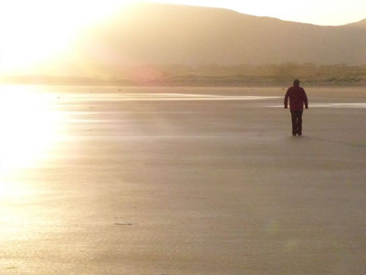 Ein Mensch geht alleine am Strand