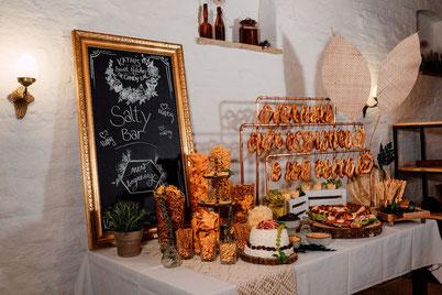 Ein Hochzeitstisch ist mit Kerzen und Blumen dekoriert.