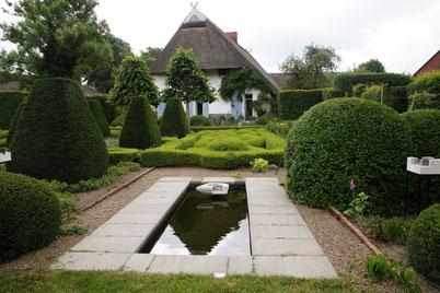 Inmitten eines kunstvoll angelegten Gartens mit in Form geschnittenen Büschen und Hecken liegt ein in Steinplatten eingefasster kleiner Teich. Auf dessen Wasseroberfläche spiegelt sich das Reetdach des im Hintergrund liegenden Hauses.