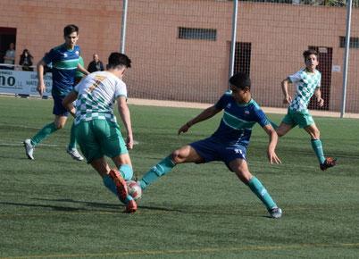 Imagen de cuatro jugadores juveniles jugando al fúbol. Dos de ellos con equipación color azul y verde y los otros dos verde y azul a cuadros. Uno de los jugadores intenta quitarle el balón al de blanco y verde de forma brusca.