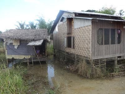 Ci contre, Miss Lha Lha Kyi revenant de son travail (vente ambulante de mohinca, le plat traditionnel birman). Ci-dessus, 2 huttes sur une mare boueuse permanente, dans lesquelles elle vît avec sa soeur et ses 3 petits-enfanfs qu'elle a en charge.