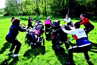 Sport mit Kinderwagen in der Natur. Mamas stehen im Kreis und machen Kniebeugen am Kinderwagen.