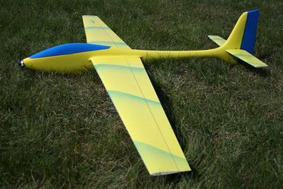 planeur Voltij Aeromod jaune et bleu primaire, posé dans l'herbe