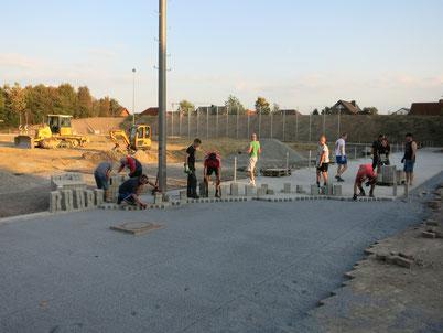 Viele fleißige Hände pflasterten rund um den neuen Rasenplatz die neue Außenanlage des SCL.