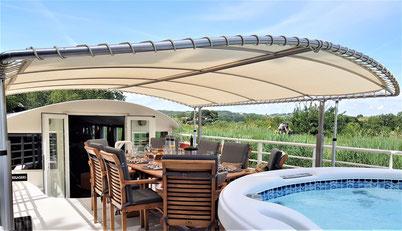 Deck der Hotelbarge Enchanté mit überdachtem Esstisch und Whirlpool