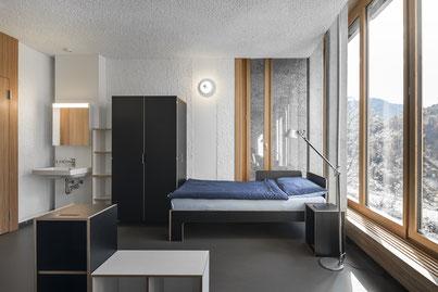 Schrank, Bett, Nachttisch und im Vordergrund Regal