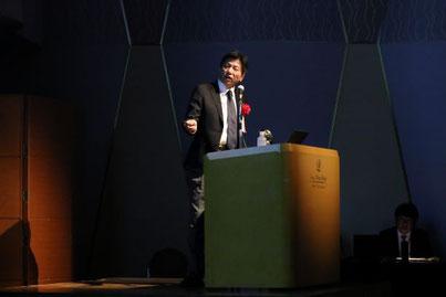 企業の経営管理者層に向けてプレゼンテーションを行うカナン株式会社の桂木夏彦