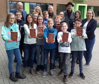 Magnus See hat die Schüler/innen mit seinen Schreibpaten gut behütet (hinten rechts). Voller Stolz präsentierten die Kinder nun ihr Erstlingswerk.