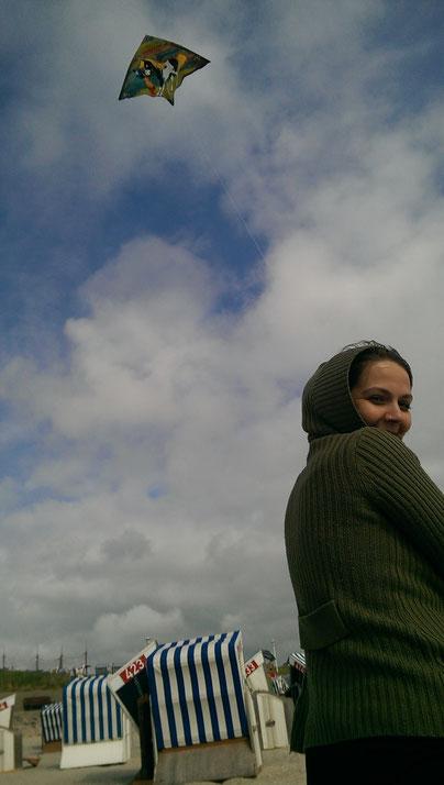 Auf dem Bild ist die Autorin zu sehen. Sie steht mit dem Rücken zur Kamera, dreht dabei den Oberkörper um und lächelt. Im Hintergrund ist zu sehen, dass sie einen Drachen steigen lässt. Und Strandkörbe sind zu sehen.