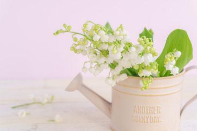 窓辺のテーブル。ロールケーキとコーヒーカップ。3時を指す置時計。窓辺は緑がいっぱいの庭。