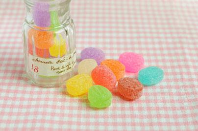 ピンクのギンガムチェックのナプキンの上に置かれたガラスの小瓶。色とりどりのドロップ。