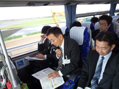 バスツアーの道中で「成田空港と圏央道整備による千葉県の発展方向と課題」について講義する小松経済活性化部会長(ちばぎん総合研究所調査部部長)