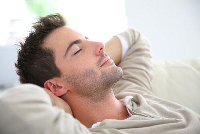 Ein Mann liegt ganz entspannt mit geschlossenen Augen und mit hinter dem Kopf verschränkten Händen auf einer Couch.