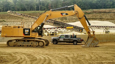 Raveling Companies bucket at work site on CAT excavator.