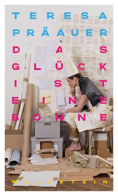 Das Bild zeigt das Cover von Das Glück ist eine Bohne von Teresa Präauer mit einer Frau inmitten von Papier und mit einer Papiermütze auf dem Kopf.