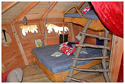 Lit double et lit superposé accessible par une échelle en bois, coussins, couvertures dans un panier, voilage rouge.