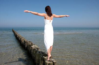balancierende Frau am Strand