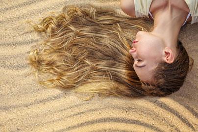 Frau mit langem Haar im Sand