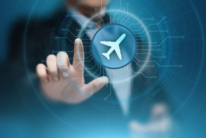 Business man touching a screen from behind with airplane icon on circular button with lines running out from airplane icon like the lines on a circuit board.