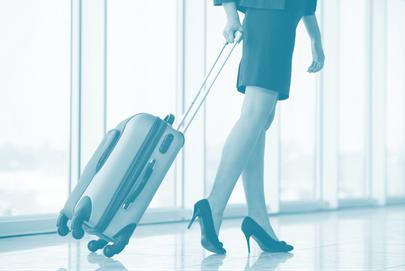 Frau zieht Rollenkoffer, Symbol für Frauen aus der Wirtschaft