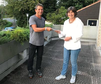 Marie Anne Niederhoff übergibt die Spende an Pfarrer Arne Stolorz