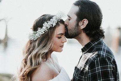 Une femme porte une couronne de fleurs. Un homme l'embrasse sur le front. Ils semblent mariés.