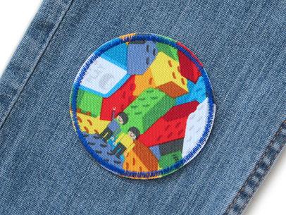 Bild: runder Stoff Hosenflicken zum aufbügeln mit vielen bunten aufgedruckten Legosteinen