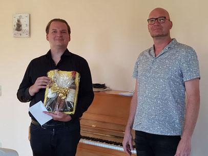 Uwe Littmann, 1. Vorsitzende der Sängerfreunde Leerstetten, gratuliert Timm Wisura (links im Bild) zum 40. Geburtstag.