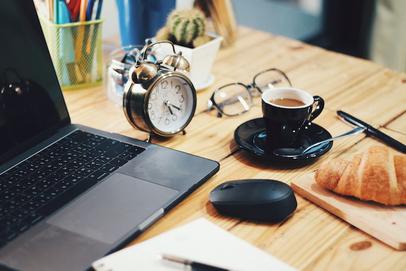 オフィスの打ち合わせテーブルでノートパソコンをひろげてミーティング中のビジネスパーソン。