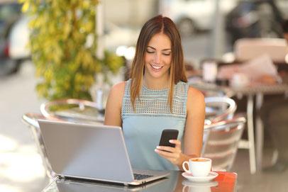 Junge Frau mit Laptop und Smartphone