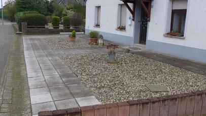 Hauseingan mit Betonplatten und Schotterflächen, drei traurige Pflanzen in Steintöpfen