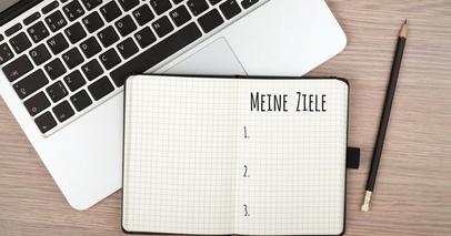 """Laptop und geöffnetes Notizbuch, in dem """"Meine Ziele"""" geschrieben ist."""