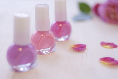 マゼンダピンク、ラズベリー、ラベンダーのマニキュアボトル。ピンクのバラの花。
