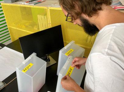 Bernhard von Unterschied und Macher beklebt die Boxen, in denen im Büro Utensilien aufbewahrt werden können (c) UuM