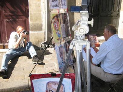 Man sieht Peter Bach jr. im Hintergrund auf dem Gehweg sitzend. Vorne ist eine Staffelei mit Künstler und einem Kamera-Stativ zu sehen. Der Künstler malte rechts im Bild. Auf der Staffelei sind fertige Gemälde zu sehen.