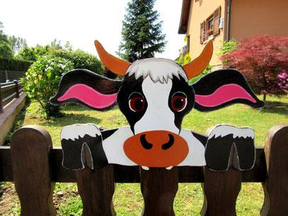 Vache en bois dans son jardin