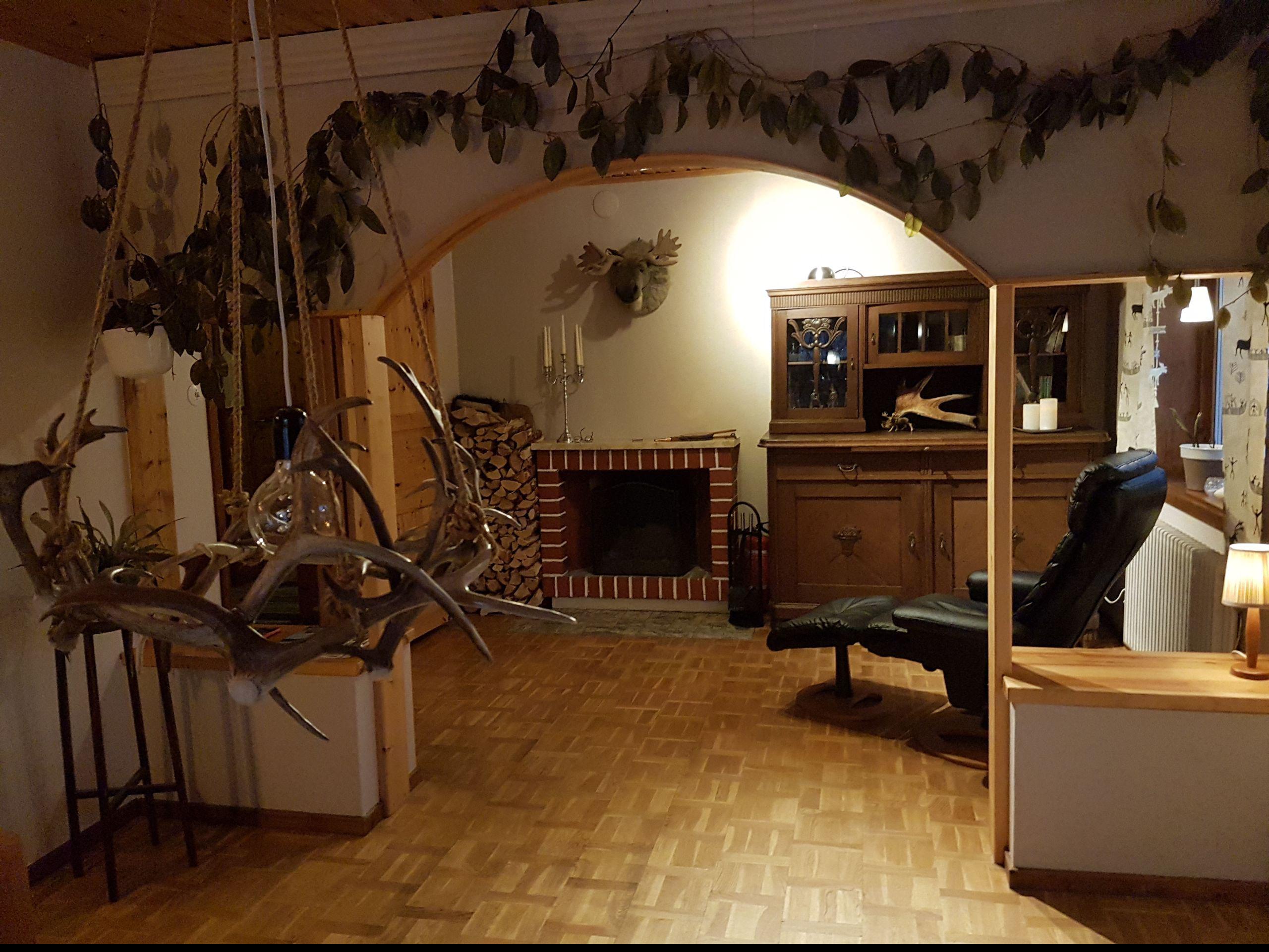 Uriges Wohnzimmer im Lapplandstil mit offenem Kamin, Relaxsessel